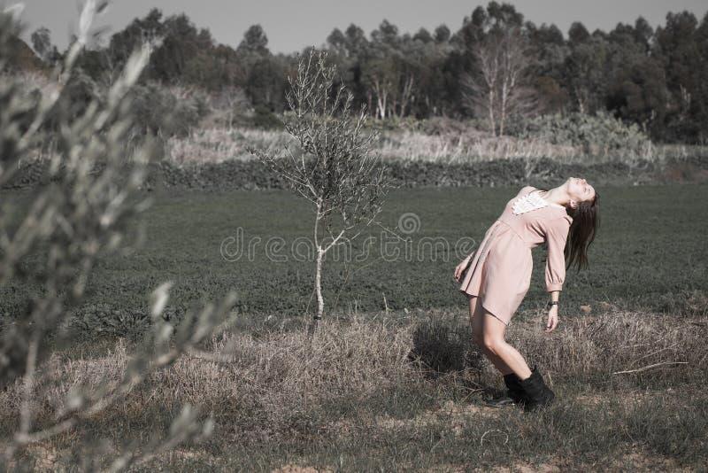 A mulher de Yoyng arqueou o levantamento modelo para trás estando do campo foto de stock