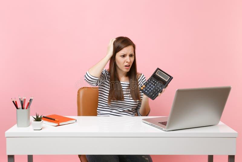 A mulher debilitada nova que adere-se para dirigir guardar a calculadora para sentar-se, trabalha no projeto no escritório com o  foto de stock