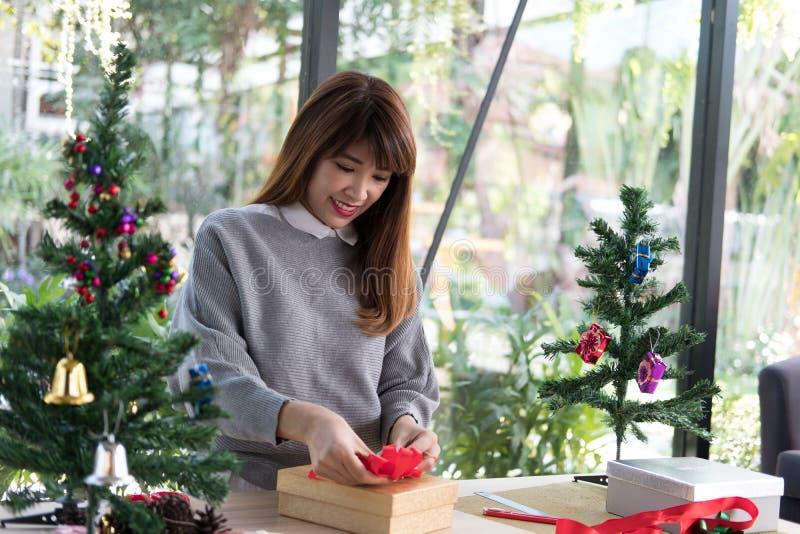 A mulher decora a caixa de presente do xmas com fita cumprimentos da estação para w fotografia de stock royalty free