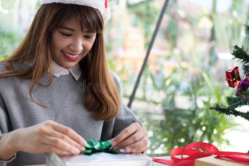 A mulher decora a caixa de presente do xmas com fita cumprimentos da estação para w foto de stock royalty free