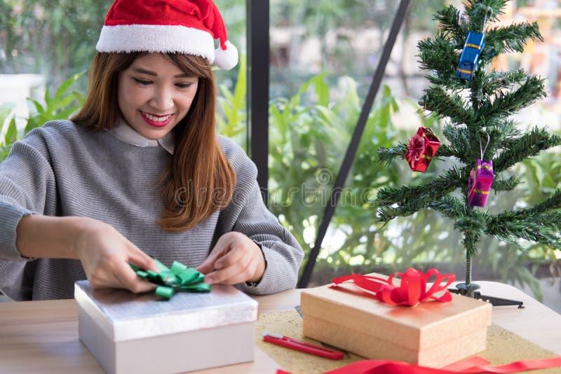 A mulher decora a caixa de presente do xmas com fita cumprimentos da estação para w imagem de stock