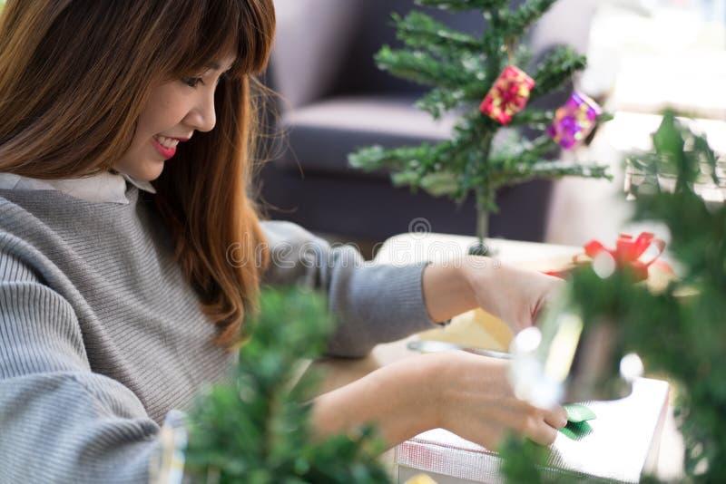 A mulher decora a caixa de presente do xmas com fita cumprimentos da estação para w imagens de stock royalty free