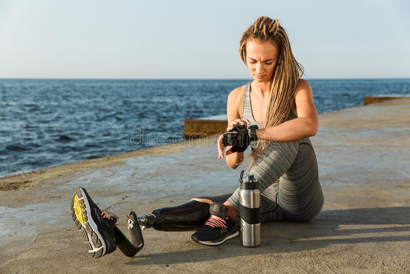 Mulher deficiente de sorriso do atleta com pé protético imagens de stock