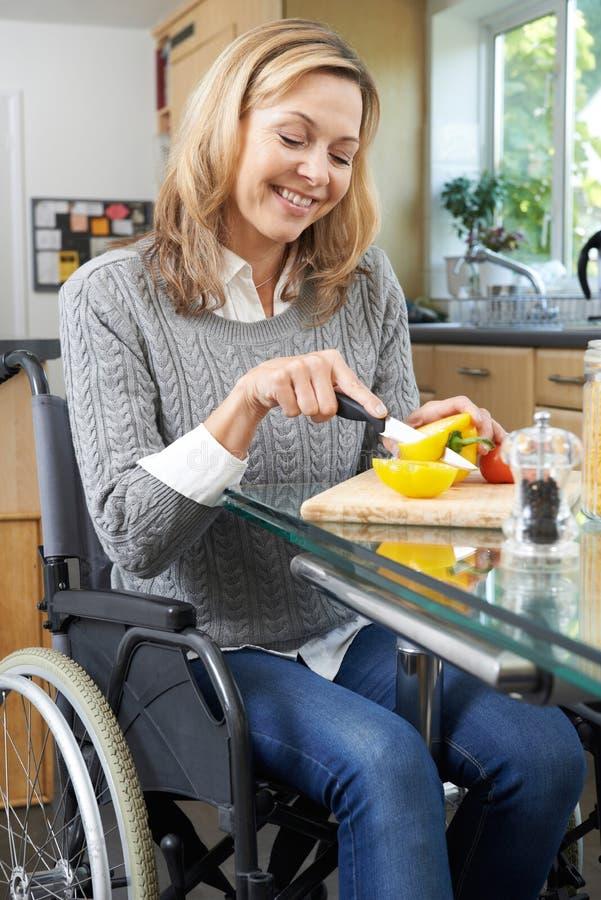 Mulher deficiente na cadeira de rodas que prepara a refeição na cozinha fotos de stock royalty free