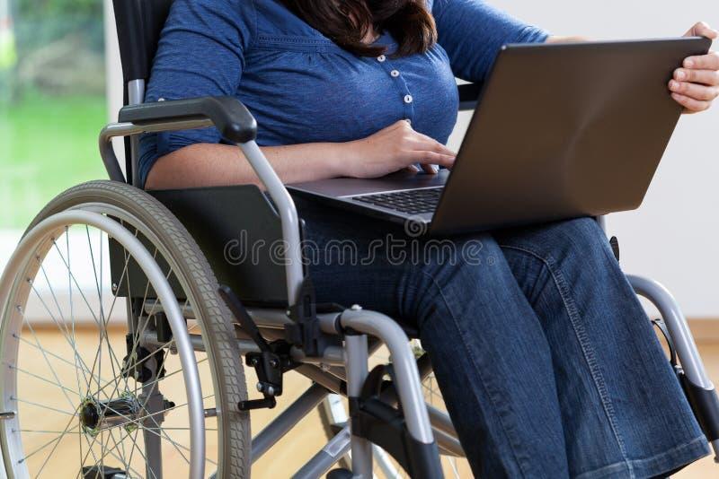 Mulher deficiente na cadeira de rodas usando o portátil fotos de stock