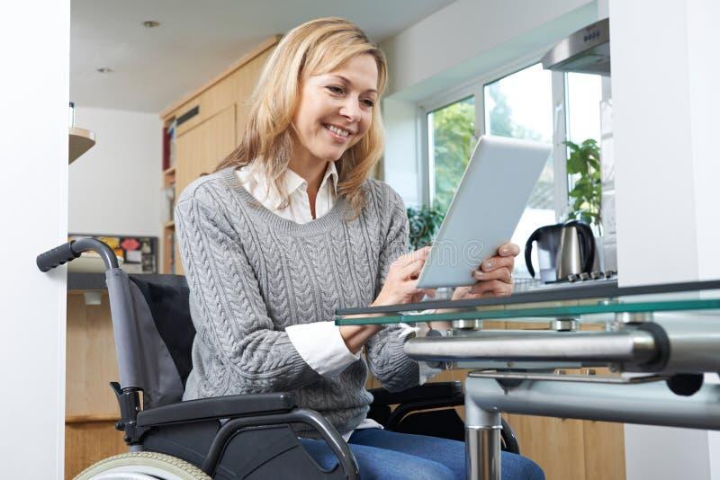Mulher deficiente na cadeira de rodas usando a tabuleta de Digitas em casa foto de stock royalty free