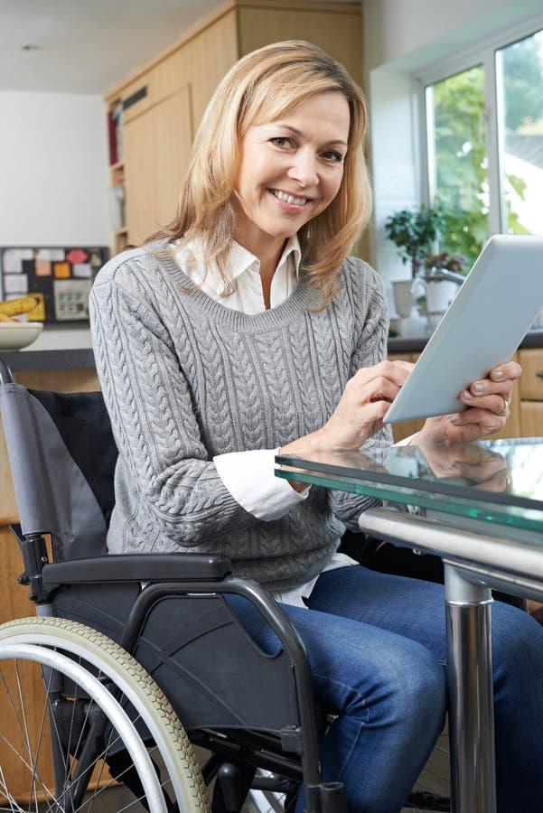 Mulher deficiente na cadeira de rodas usando a tabuleta de Digitas em casa imagens de stock