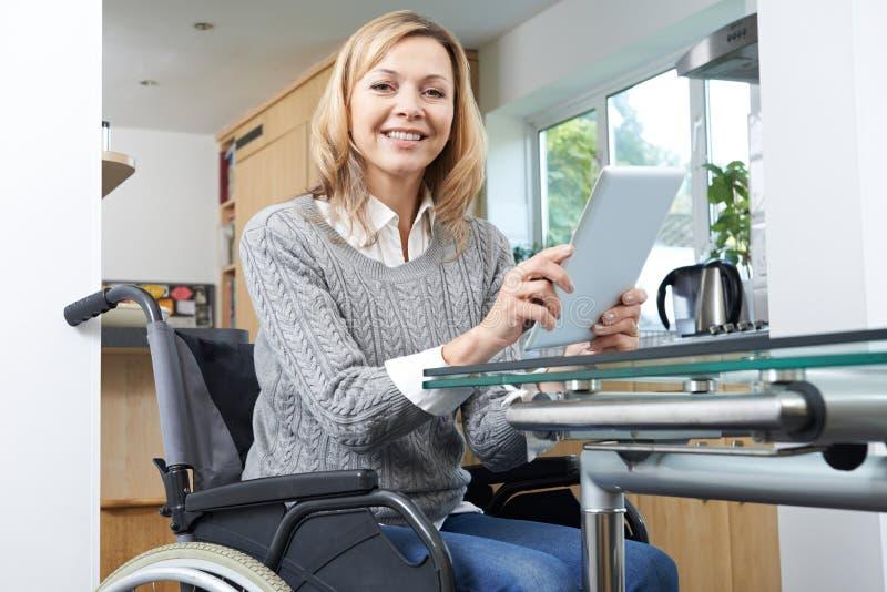 Mulher deficiente na cadeira de rodas usando a tabuleta de Digitas em casa fotografia de stock