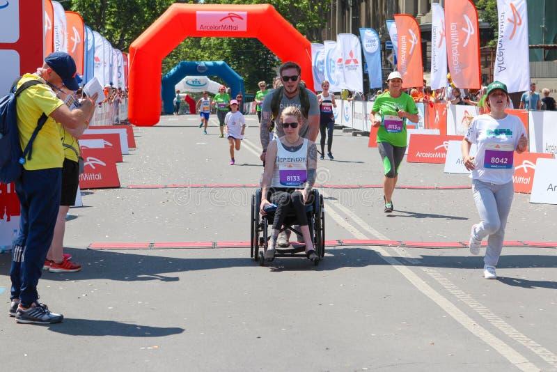 Mulher deficiente na maratona em uma cadeira de rodas Corredor deficiente na maratona imagem de stock