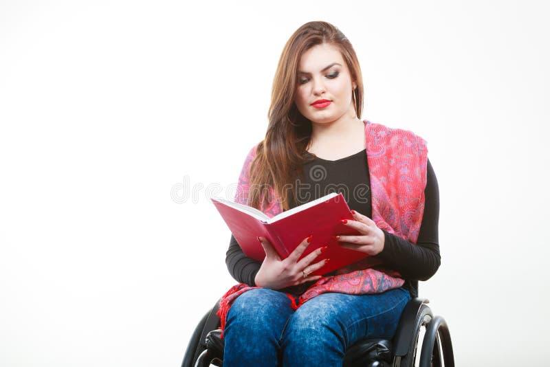 Mulher deficiente nova na cadeira de rodas com livro foto de stock royalty free