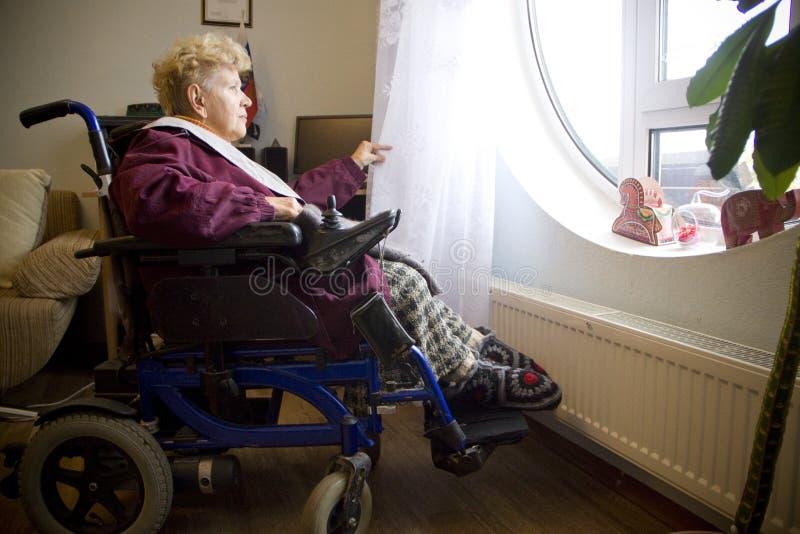 A mulher deficiente olha para fora a janela imagem de stock royalty free
