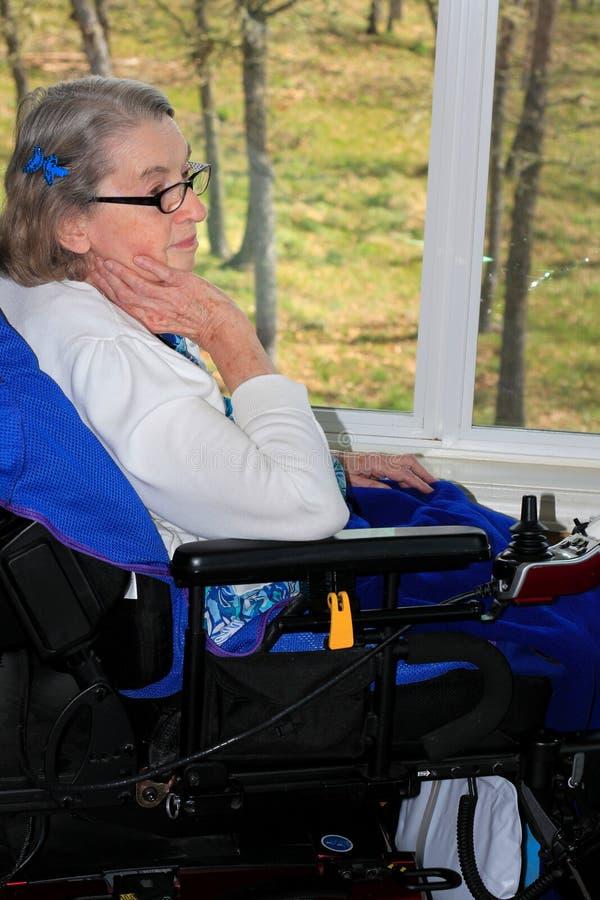 Mulher deficiente pela janela imagem de stock