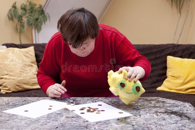 Mulher deficiente que olha desesperadamente para pouco dinheiro fotografia de stock