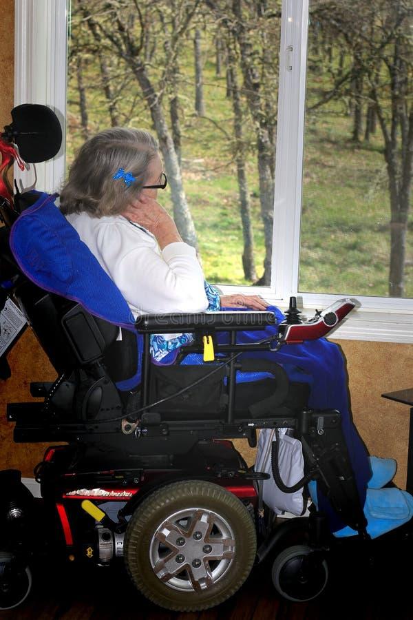 Mulher deficiente que olha para fora a janela foto de stock