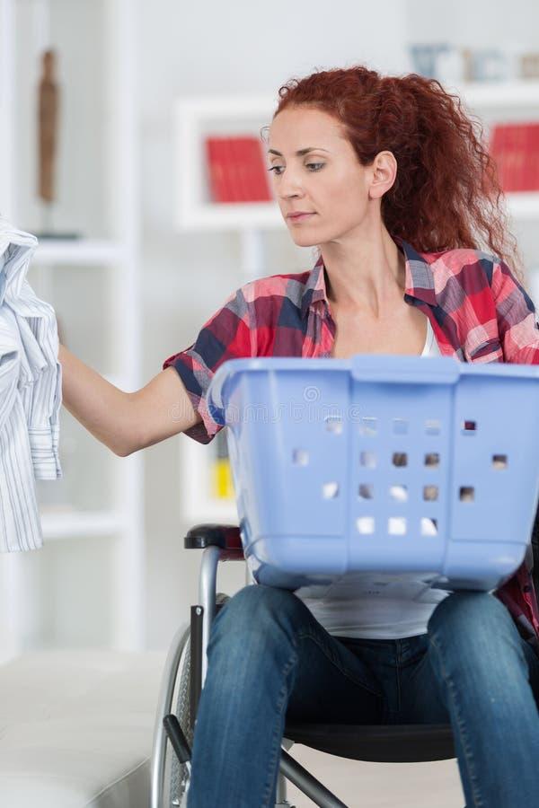 Mulher deficiente que senta-se na cadeira de rodas que faz a lavanderia em casa imagens de stock