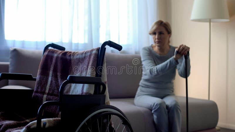 Mulher deficiente só que senta-se no sofá e que olha a cadeira de rodas vazia, memórias fotografia de stock