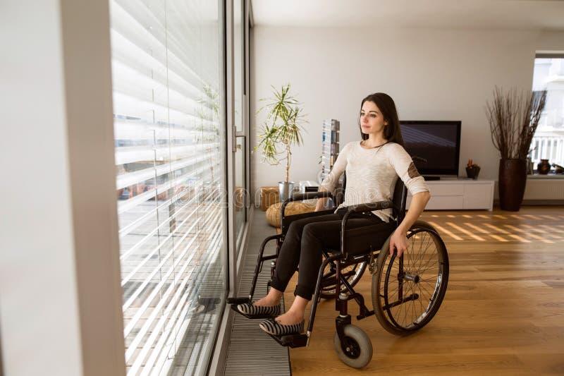 Mulher deficiente virada na cadeira de rodas em casa na sala de visitas imagens de stock royalty free