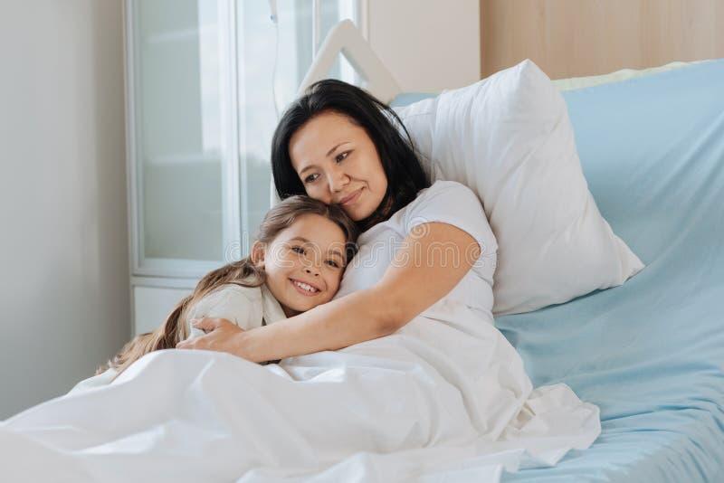 Mulher deleitada agradável que abraça sua criança fotografia de stock