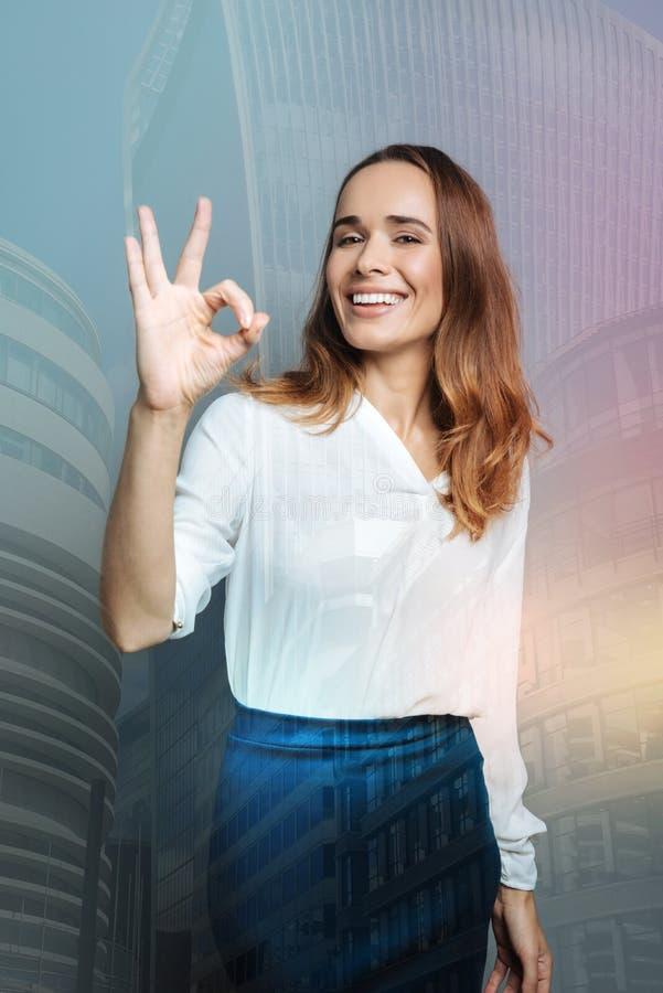 Mulher deleitada feliz que mostra o gesto APROVADO imagem de stock