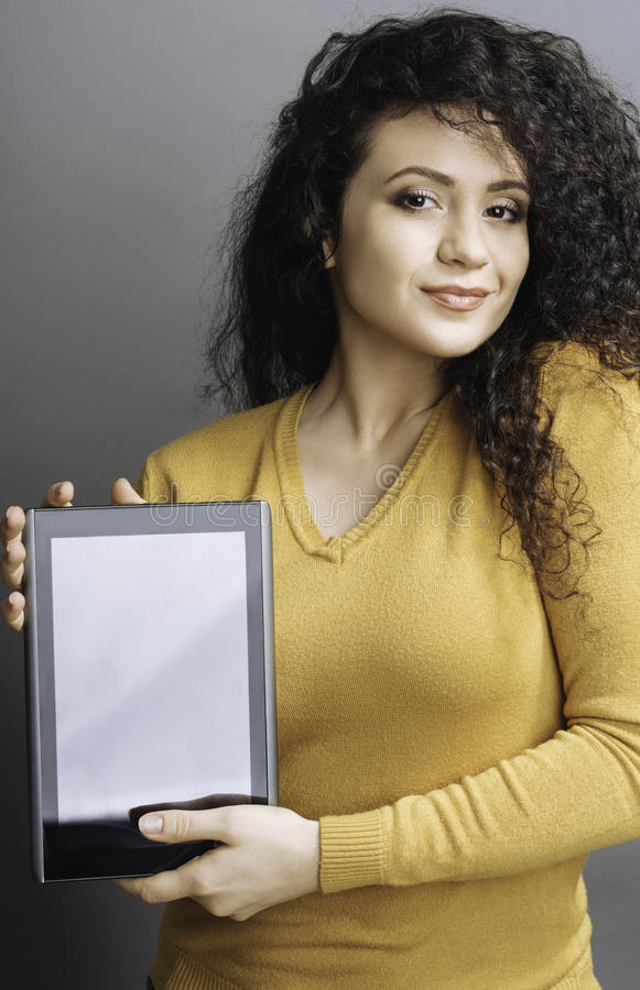Mulher deleitada que mantém a tabuleta em ambas as mãos foto de stock