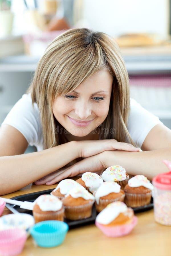 Mulher deleitada que olha bolos na cozinha imagens de stock royalty free