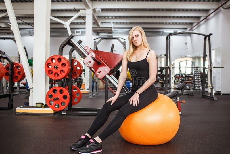 Mulher delgada desportiva nova no gym que levanta na bola alaranjada em um fundo do instrumento do gym fotografia de stock