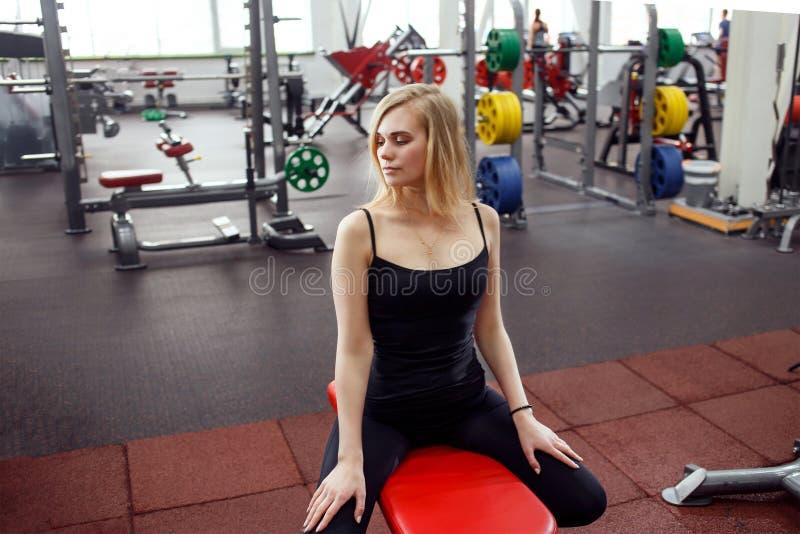 Mulher delgada nova no gym que levanta contra muito equipamento da aptidão no fundo Veste o t-shirt preto, calças e fotografia de stock royalty free