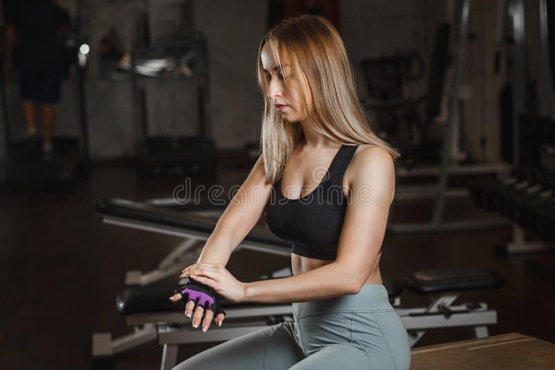 Mulher delgada nova que prepara-se para os esportes que treinam e que põem sobre suas luvas dos esportes no gym fotos de stock royalty free