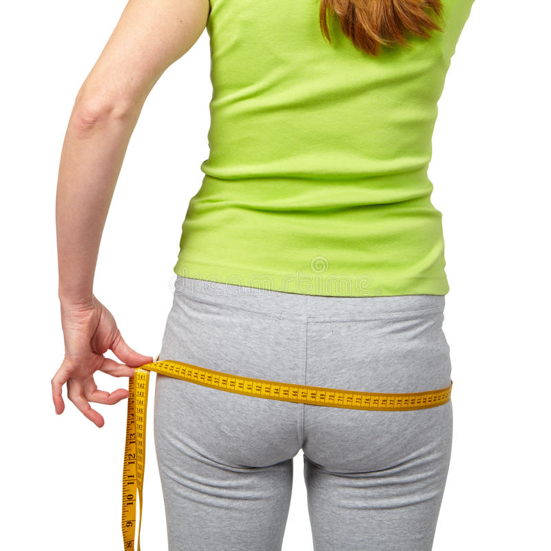 Mulher delgada que mede sua cintura imagem de stock