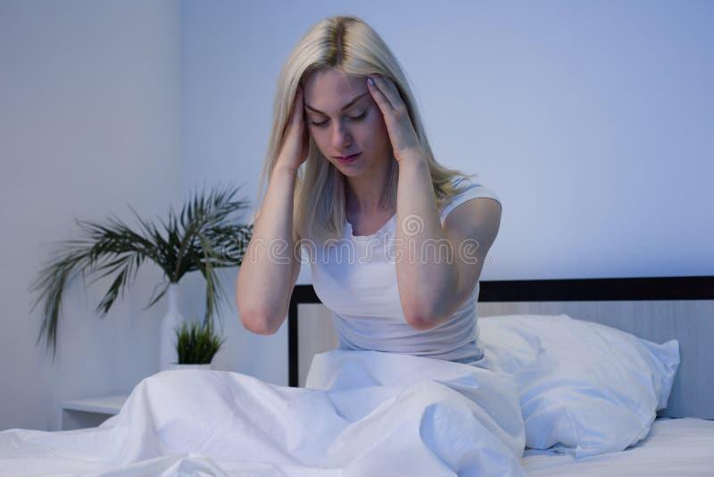 Mulher deprimida acordada na noite, ? esgotada e de sofrimento da ins?nia fotos de stock