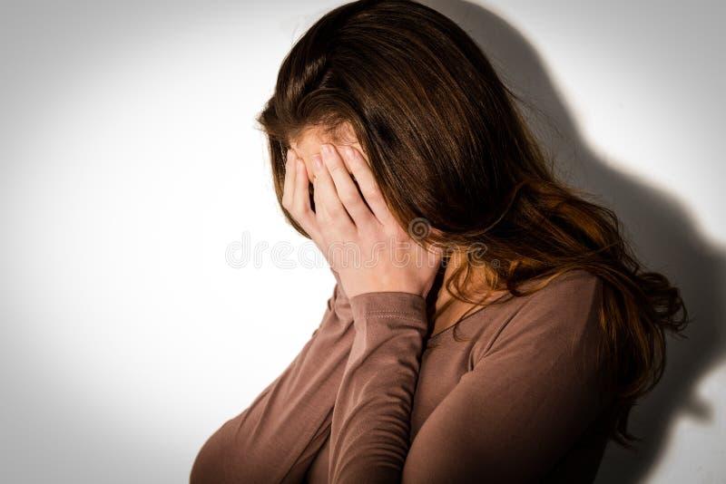 Mulher deprimida com cabeça nas mãos imagens de stock royalty free