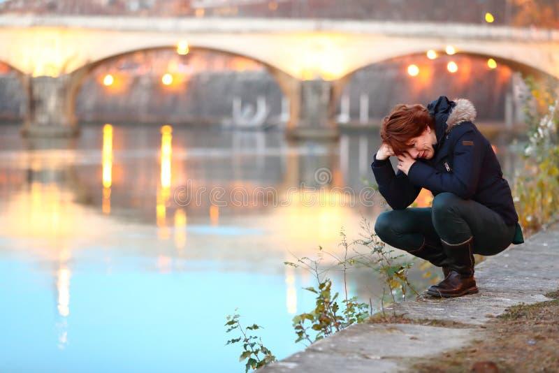 Mulher deprimida que ajoelha-se pela margem em uma cidade próximo uma ponte que grita e que sente só imagens de stock