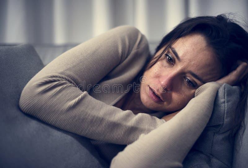 Mulher deprimida que encontra-se no sofá imagens de stock royalty free