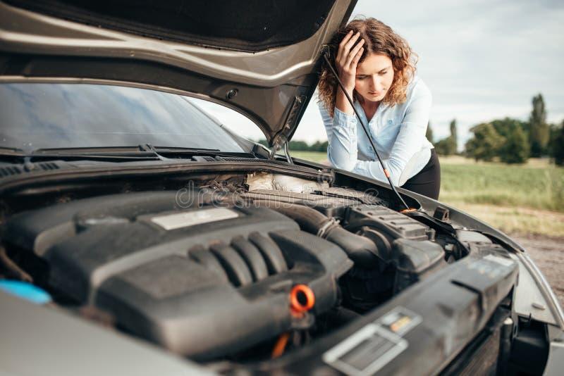 Mulher deprimida que olha o motor, carro quebrado imagem de stock royalty free
