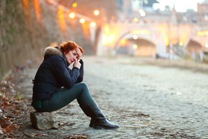 Mulher deprimida que senta pela margem em uma cidade próximo uma ponte que grita e que sente só fotografia de stock