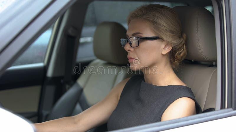Mulher deprimida que senta-se no carro no lugar do motorista, pensando sobre problemas da vida imagens de stock royalty free