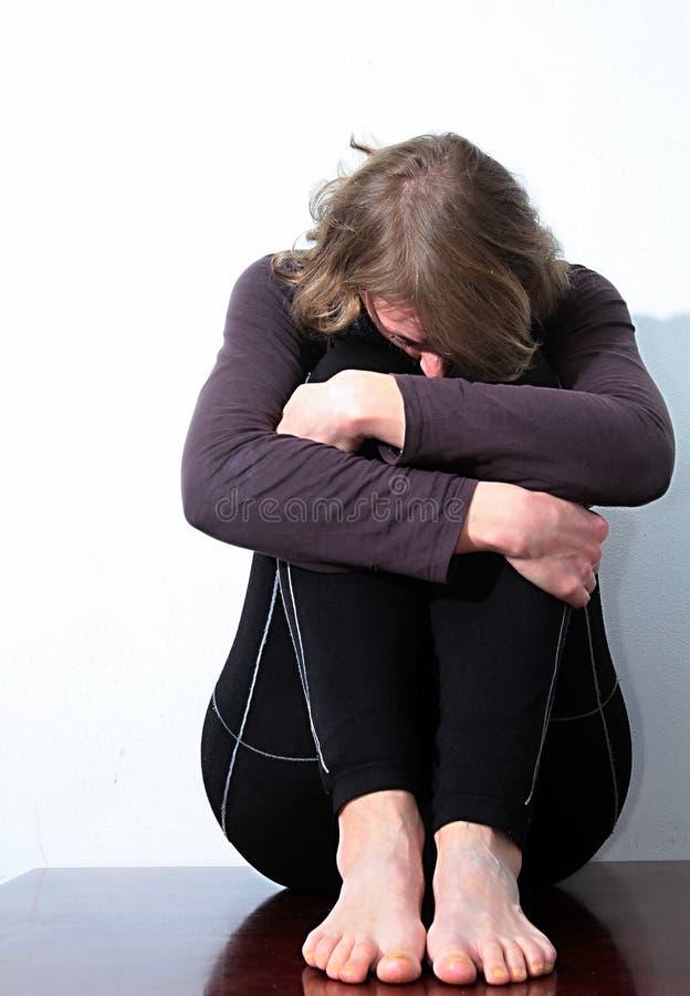 Mulher deprimida que sente para baixo fotografia de stock royalty free