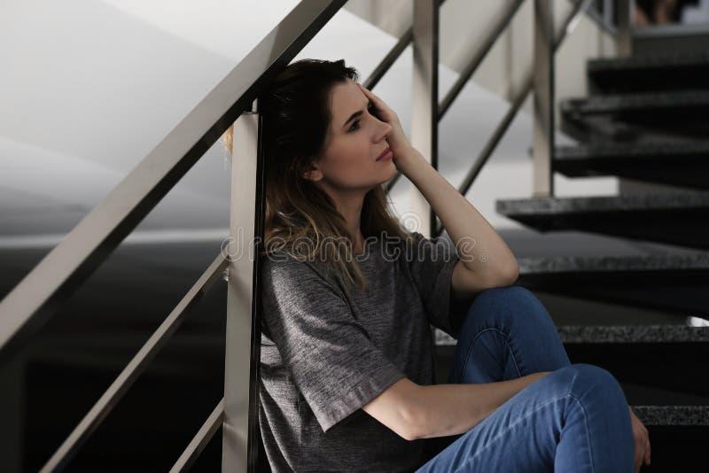 Mulher deprimida só que senta-se em escadas foto de stock