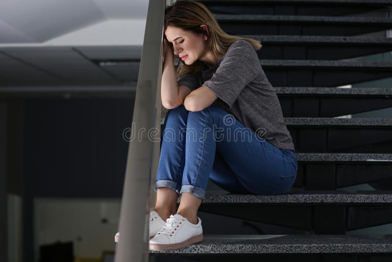 Mulher deprimida só que senta-se em escadas foto de stock royalty free