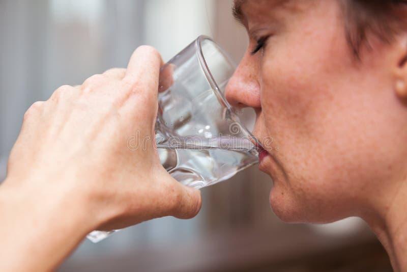 A mulher derrama a água fresca em um vidro foto de stock royalty free