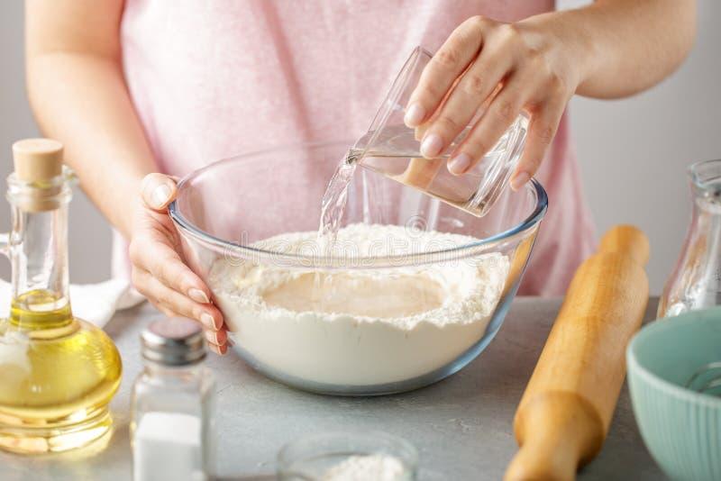 A mulher derrama a água quente na bacia com farinha, fermento em pó, sal e óleo imagens de stock
