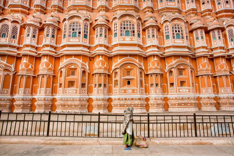 Mulher desabrigada pobre que está na parte dianteira do palácio de pedra vermelho fotos de stock royalty free
