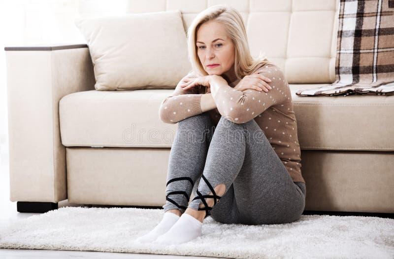 Mulher descalça envelhecida meio que senta-se no assoalho que abraça seus joelhos, perto do sofá em casa, sua cabeça para baixo,  imagens de stock