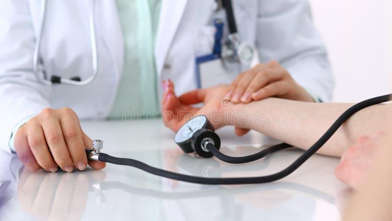 Mulher desconhecida do doutor que verifica a press?o sangu?nea do paciente f?mea, close-up Cardiologia no conceito da medicina e  fotos de stock royalty free