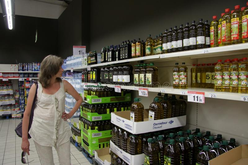 A mulher desconhecida escolhe o azeite na loja imagens de stock royalty free