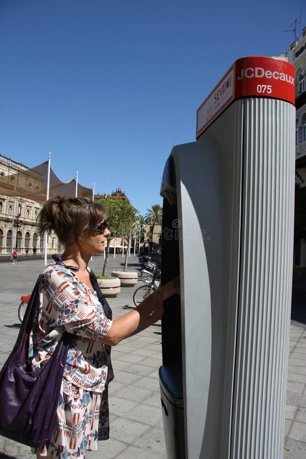 Mulher desconhecida na máquina do bilhete para bicicletas municipais imagens de stock royalty free