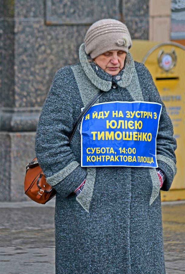 Mulher desconhecida no revestimento cinzento com as pre-eleições de Julia Timoshenko que encontram a mensagem em Kiev, Ucrânia, imagens de stock