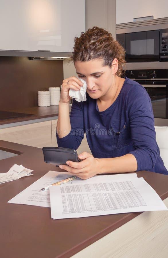 Mulher desempregada com contas mensais da revisão dos débitos imagem de stock