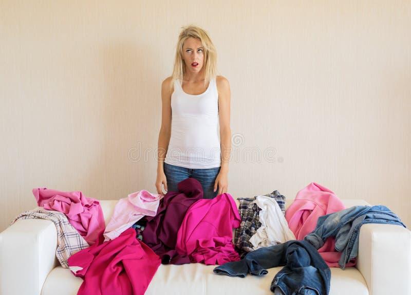 Mulher desesperada ao lado da pilha desarrumado de roupa no sofá foto de stock