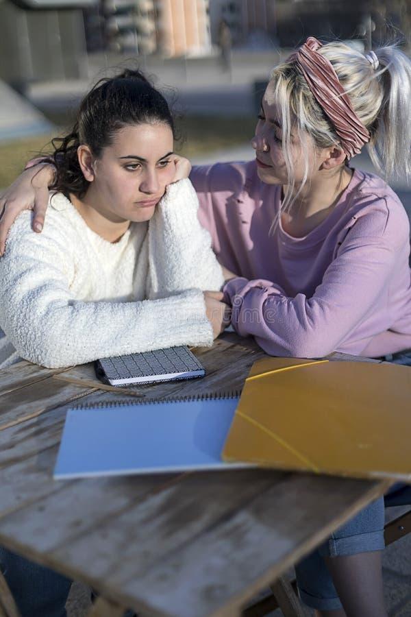Mulher desesperada do estudante que obtém o apoio de seu melhor amigo que senta-se fora foto de stock